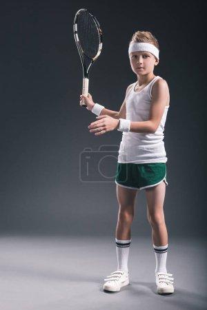 Foto de Centrado niño en ropa de deporte con raqueta de tenis en fondo oscuro - Imagen libre de derechos