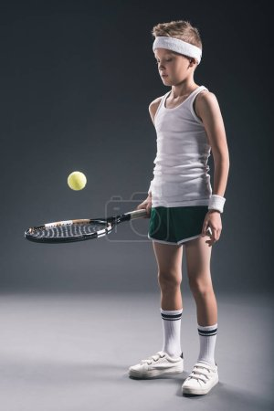 preteen boy in sportswear with tennis racket and ball on dark background