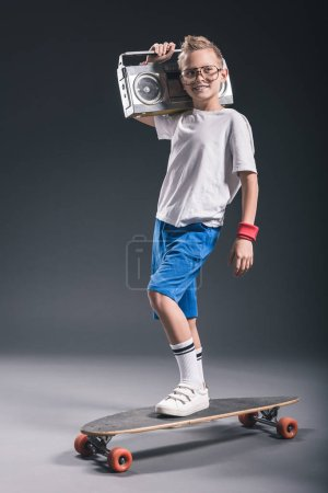 Photo for Smiling boy with boombox on shoulder standing on longboard on grey background - Royalty Free Image