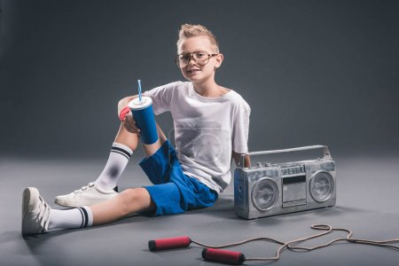 Photo for Boy in eyeglasses with soda drink, boombox and jump rope on grey backdrop - Royalty Free Image