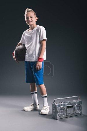 stylish boy with basketball ball and boombox on grey backdrop