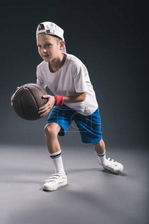 stylish boy playing basketball on grey background