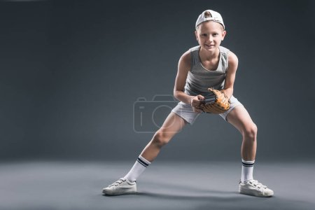 preteen boy in cap with baseball glove and ball on grey backdrop