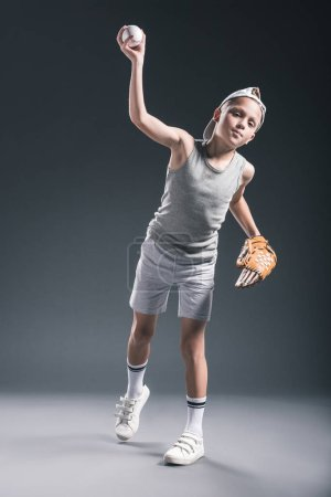 preteen boy in cap with baseball glove throwing ball on grey backdrop