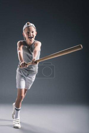 emotional preteen boy in cap with baseball bat on grey background