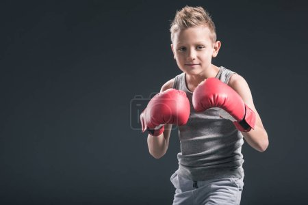 portrait of boy with red boxing gloves on black backdrop
