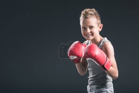 Photo for Portrait of cheerful boy with red boxing gloves on black backdrop - Royalty Free Image