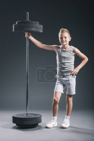 Photo for Smiling pre-adolescent boy in sportswear standing near barbell on dark backdrop - Royalty Free Image
