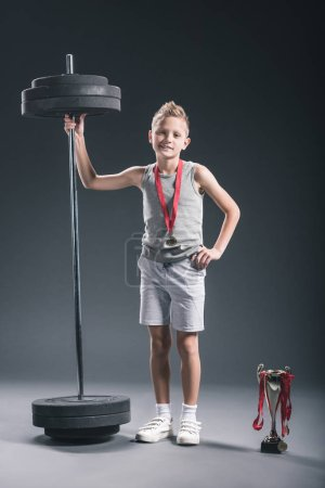 pre-adolescent boy in sportswear with barbell, champions cup and medals on dark backdrop