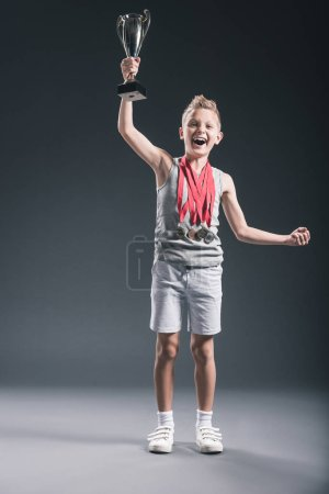 happy boy in sportswear with medals and champions cup gesturing on dark background