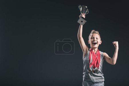 portrait of happy boy in sportswear with medals and champions cup gesturing on black background