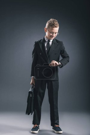 preteen boy in businessman suit and eyeglasses with suitcase checking time on dark background