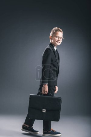 side view of preteen boy in businessman suit and eyeglasses with suitcase on dark background