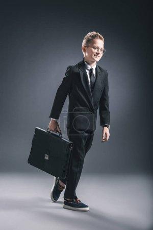 Photo pour Préadolescent garçon en costume d'homme d'affaires et lunettes avec valise marchant sur fond sombre - image libre de droit