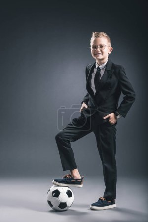 smiling boy dressed as businessman with soccer ball looking at camera on grey background