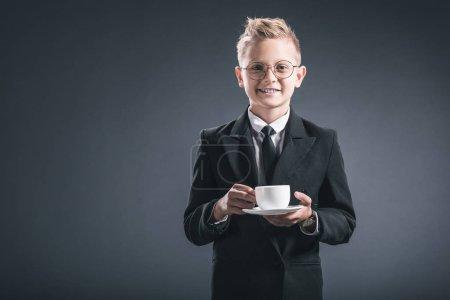 Foto de Retrato de niño sonriente empresario traje y anteojos que con taza de café sobre fondo oscuro - Imagen libre de derechos