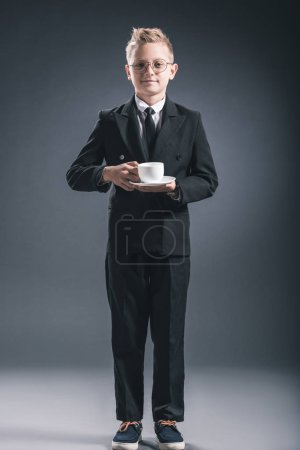 Photo for Boy in businessman suit and eyeglasses holding cup of coffee on dark backdrop - Royalty Free Image