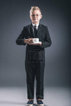 Photo pour Garçon en costume d'homme d'affaires et de lunettes de vue tenant la tasse de café sur fond foncé - image libre de droit