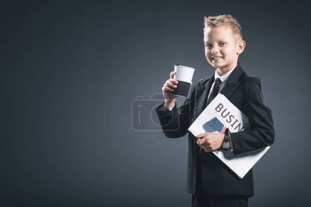 portrait of smiling boy in businessman suit with coffee to go and business newspaper on grey backdrop