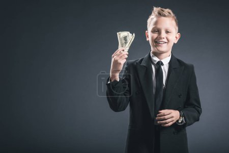 portrait of smiling preteen boy dressed as businessman holding dollar banknotes in hands on grey backdrop
