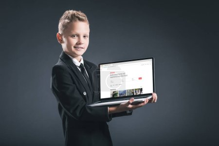 smiling boy in businessman suit showing laptop with airbnb website on screen on grey background