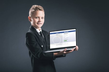 smiling boy in businessman suit showing laptop with facebook website on screen on grey background
