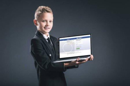 Photo pour Garçon souriant en costume d'homme d'affaires montrant ordinateur portable avec site facebook à l'écran sur fond gris - image libre de droit