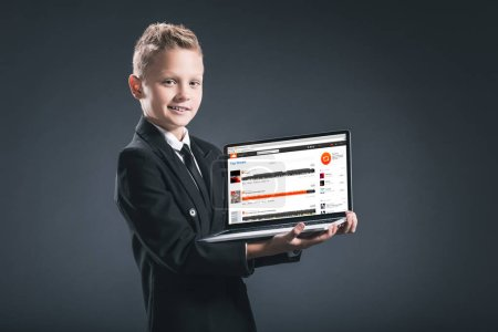 smiling boy in businessman suit showing laptop with soundcloud website on grey background