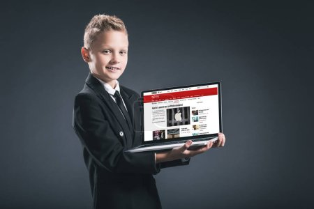 Photo for Smiling boy in businessman suit showing laptop with bbc website on grey background - Royalty Free Image