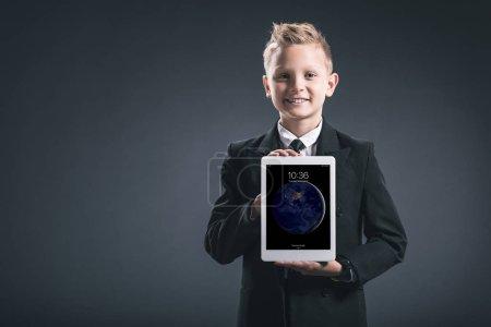 portrait of smiling boy dressed like businessman showing tablet in hands on grey backdrop