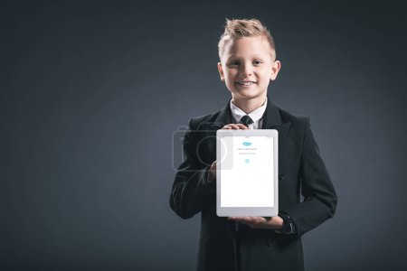 Photo for Portrait of smiling boy dressed like businessman showing tablet with sqype logo in hands on grey backdrop - Royalty Free Image