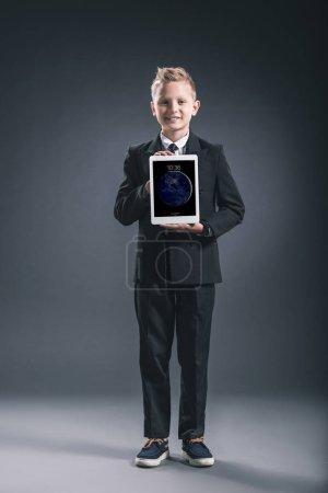 smiling boy dressed like businessman showing tablet in hands on grey backdrop