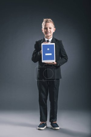 smiling boy dressed like businessman showing tablet with facebook logo in hands on grey backdrop