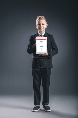 smiling boy dressed like businessman showing tablet with instagram logo in hands on grey backdrop