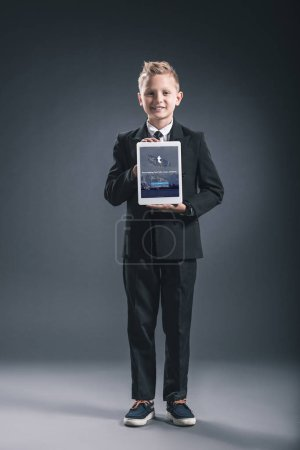 Smiling boy dressed like businessman showing tablet with tumblr logo in hands on grey backdrop
