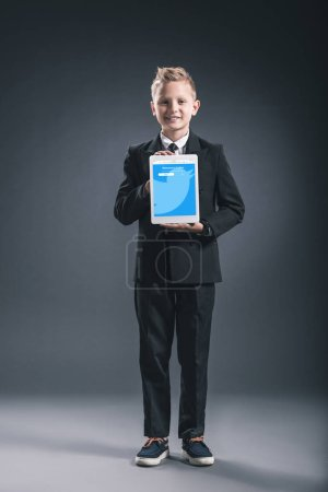 smiling boy dressed like businessman showing tablet with twitter website in hands on grey backdrop