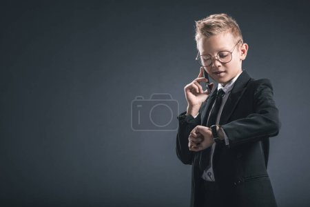 preteen boy dressed as businessman checkign time while talking on smartphone on dark background