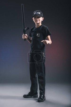 preteen boy in policeman uniform with truncheon on dark backdrop
