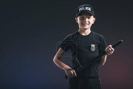 smiling preteen boy in policeman uniform with truncheon on dark backdrop