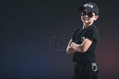 Foto de Retrato de sonriente niño en uniforme de policía y gafas de sol sobre fondo oscuro - Imagen libre de derechos
