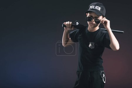 portrait of boy in policeman uniform and sunglasses with truncheon on dark background