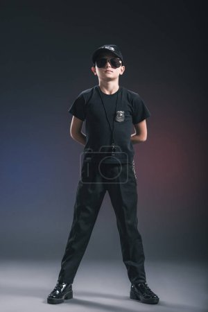 boy in policeman uniform and sunglasses with whistle on dark background
