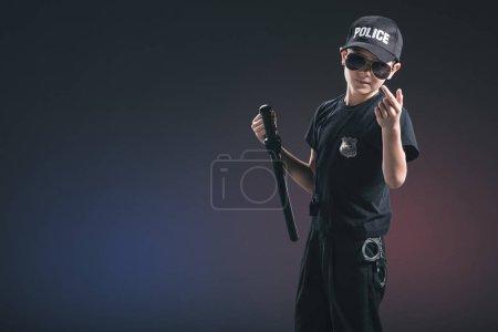 portrait of boy in policeman uniform and sunglasses gesturing on dark background