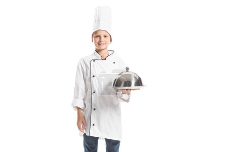 Lächelnder Junge in Kochuniform und Hut mit Metalltablett auf weißem Hintergrund