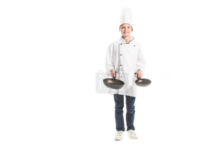 Photo for Smiling boy in white chef uniform and hat holding frying pans and looking at camera isolated on white - Royalty Free Image