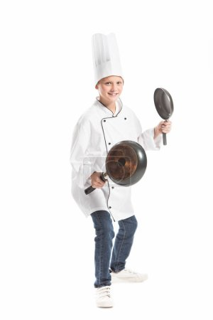 Photo for Boy in white chef uniform and hat holding frying pans isolated on white - Royalty Free Image