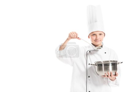 pre-adolescent boy in chef uniform with saucepan and ladle isolated on white