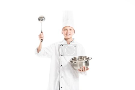 Photo for Pre-adolescent boy in chef uniform with saucepan and ladle isolated on white - Royalty Free Image