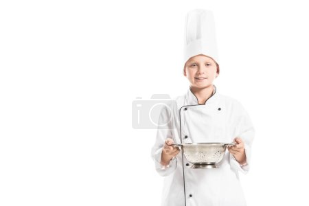 portrait of smiling boy in white chef uniform with colander isolated on white