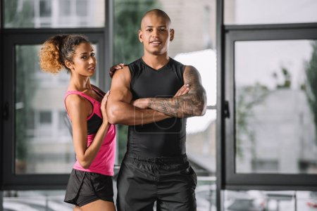 smiling young african american male athlete posing with crossed arms while his girlfriend standing near at gym